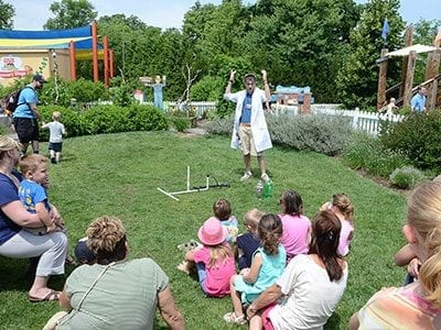 Image of children watching a demonstration in the backyard section of Natures Neighborhood