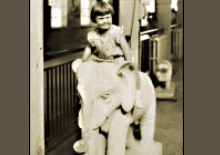 Historic photo of a girl on an elephant statue