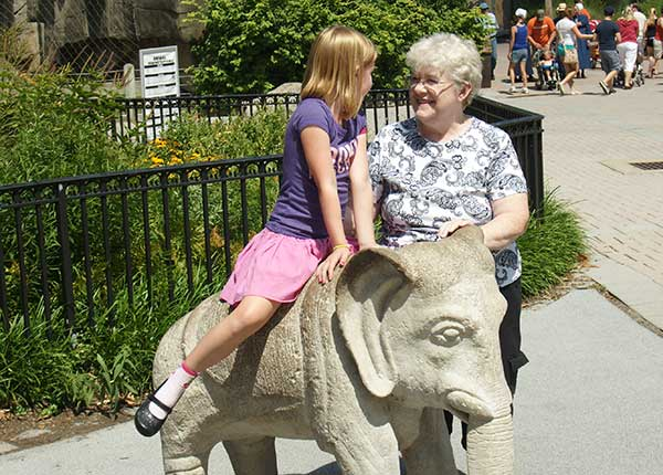 Image of a grandmother with her granddaughter on an elephant statue